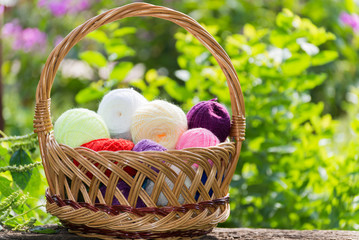 Wicker basket with colorful balls of yarn