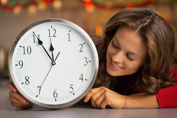 Portrait of happy young housewife looking on clock