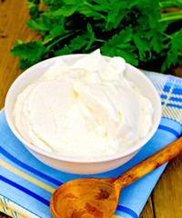 Yogurt in white bowl with greens on board