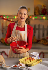 Portrait of smiling young housewife whisking dough