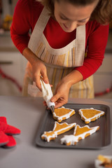 Closeup on young housewife making christmas cookies