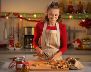Happy young housewife chopping walnuts