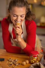 Portrait of happy young housewife eating walnuts