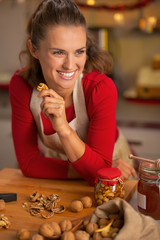 Portrait of smiling young housewife eating walnuts