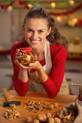 Portrait of happy young housewife showing jar with honey nuts