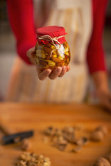 Closeup on young housewife holding jar with honey nuts