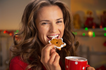 Portrait of happy young woman eating christmas snacks