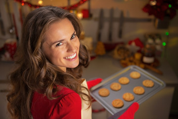 Portrait of smiling young housewife with pan of fresh cookies