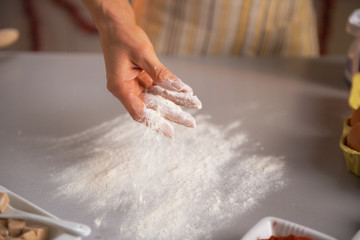 Closeup on young housewife sprinkling flour on table