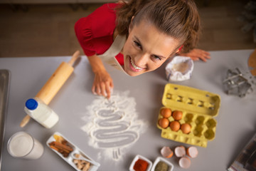 Happy young housewife drawing christmas tree with flour on table