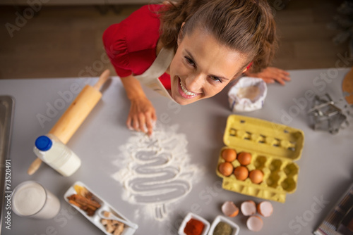 Foto op Plexiglas Koken Happy young housewife drawing christmas tree with flour on table