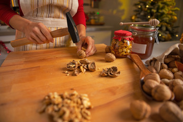 Closeup on young housewife chopping walnuts in kitchen