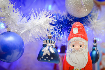 White and blue christmas toys on pine tree and Santa Claus