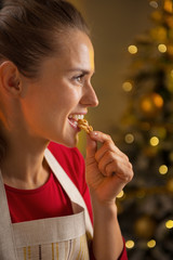 Profile portrait of happy young housewife eating walnuts