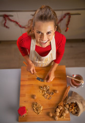 Portrait of happy young housewife chopping walnuts