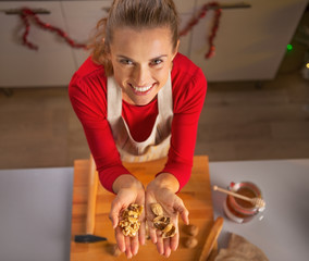 Happy young housewife showing walnuts in kitchen