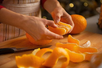 Closeup on young housewife dividing orange slices