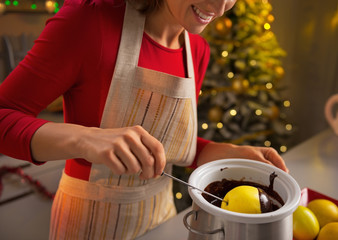 Closeup on young housewife making apple in chocolate glaze