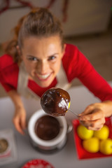 Closeup on housewife showing homemade apple in chocolate glaze