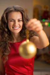 Portrait of happy young housewife showing christmas ball