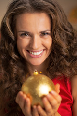 Portrait of smiling young housewife holding christmas ball