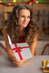 Portrait of happy young woman with christmas postcard in kitchen