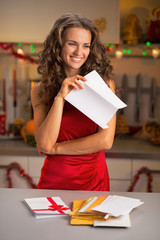 Happy young housewife holding letter