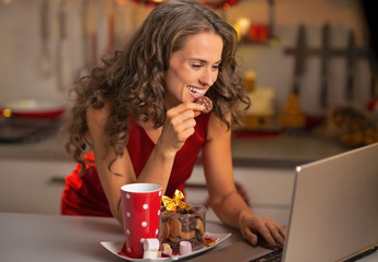 Happy young housewife with christmas snacks using laptop