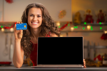 Happy young woman with credit card showing laptop blank screen