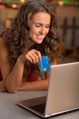 Portrait of happy young woman with credit card using laptop