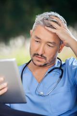 Tensed Male Caretaker Using Tablet PC