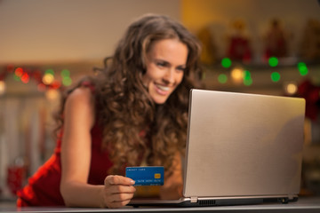 Closeup on happy young woman with credit card using laptop