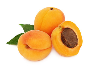Two whole and a half apricot with leaves (isolated)