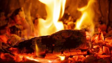 Close-up glowing coals in the fireplace with a flame