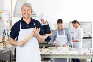 Happy Chef Holding Rolling Pin While Colleagues Preparing Pasta