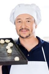 Smiling Chef Carrying Baking Sheet With Dough Balls
