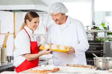 Smiling Chefs Holding Pasta Tray In Kitchen