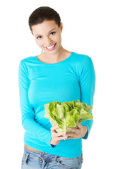 Happy young woman holding lettuce