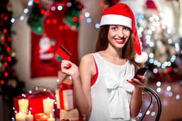 Young woman buying gifts with credit card on Christmas