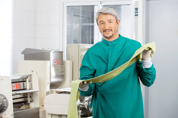 Male Chef Holding Green Spaghetti Pasta Sheet By Machine