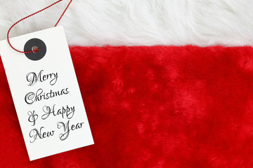 Christmas wishes on white tag on santas red fur