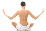 Back view of a woman in towel practising yoga