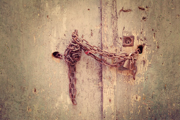 rusty metal chain on a wooden door