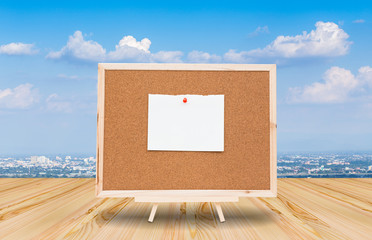 Blank paper note on cork board with blue sky background