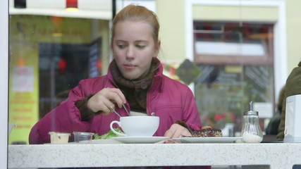 Girl eating light salad at cafe diner on a city street