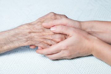 Caregiver holds hands of an old man. Closeup.