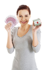 Happy woman holding house model and euro bills