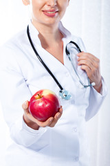 Female doctor giving red apple