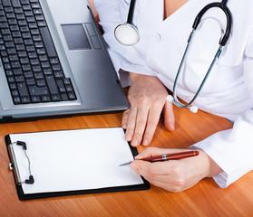 Female doctor showing blank clipboard