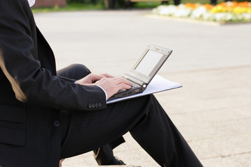 Businessman working on computer and working paperwork outside